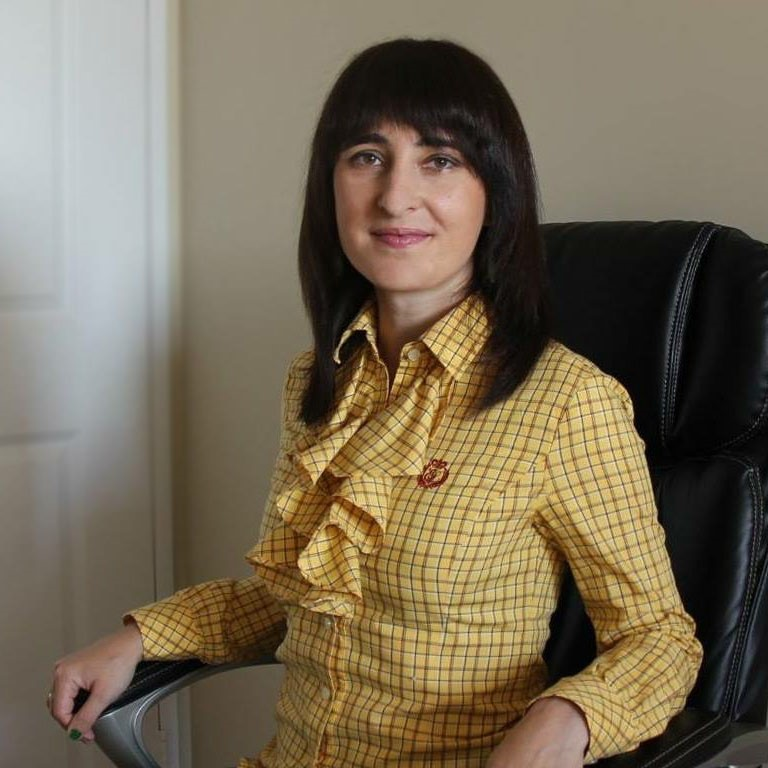 This is a headshot image of Elizaveta Dolgova. She is sitting in the office chair. She wears a yellow business casual shirt.