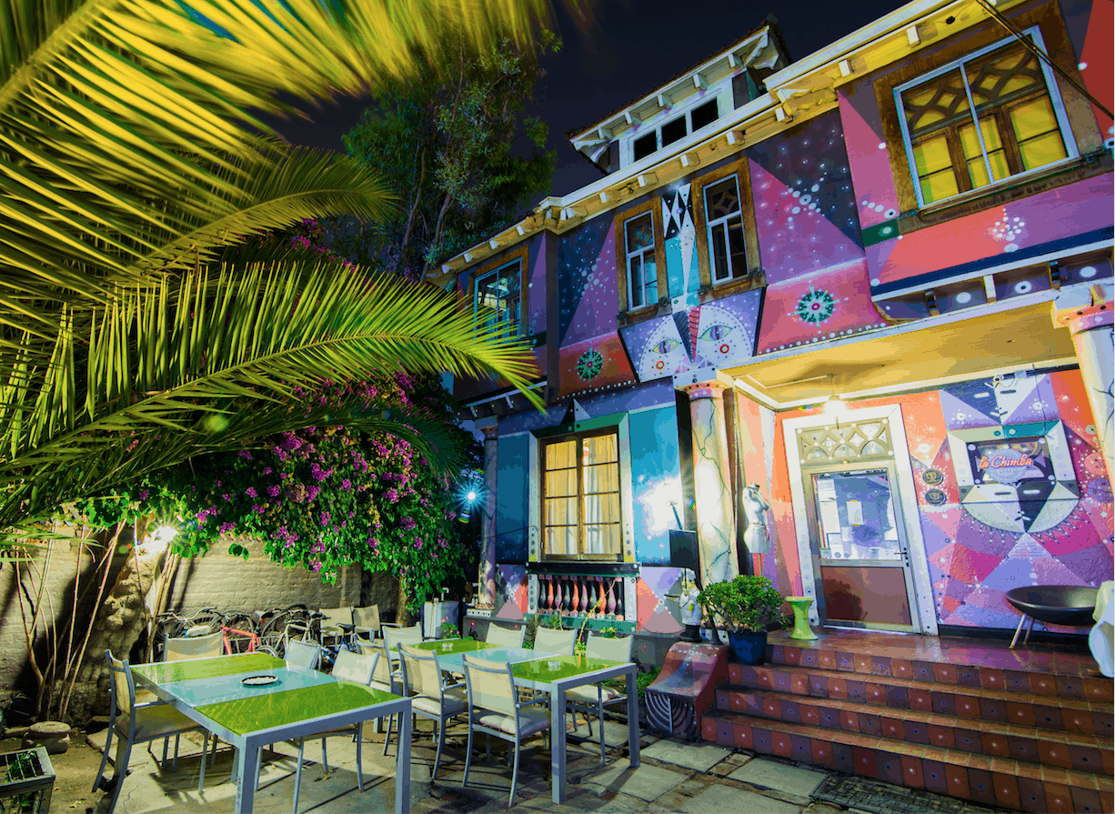 A colourful painted building and a patio outside at night