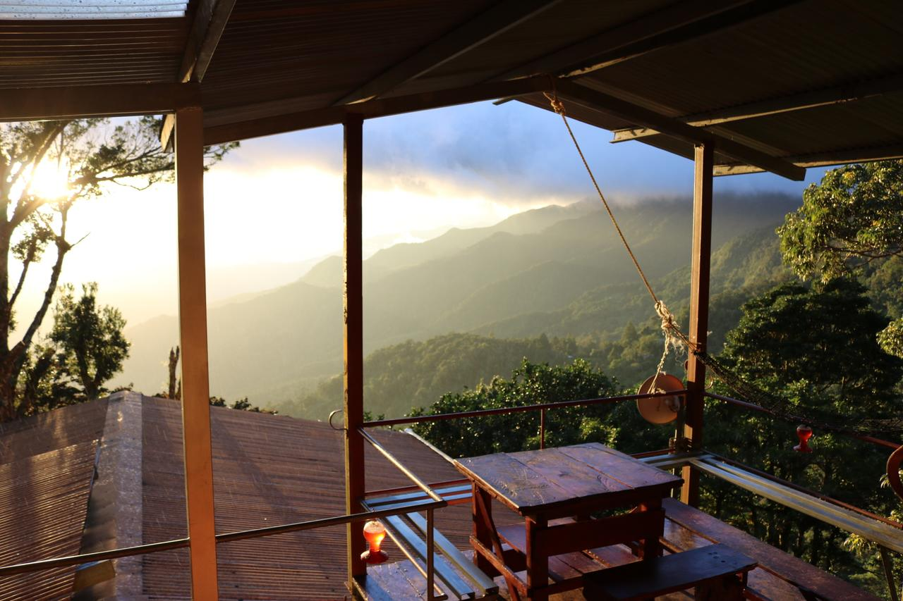 The open balcony of the Lost and Found Hostel, looking out onto a green valley, the sun is setting