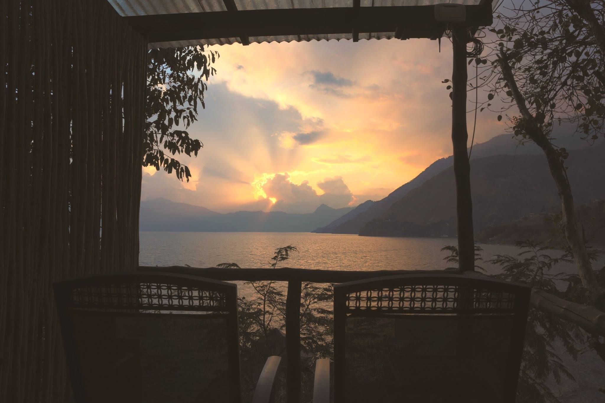 Orange sunset behind clouds, from a wooden balcony overlooking Lake Atitlan