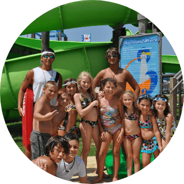 group of young kids posing in front of a green waterslide