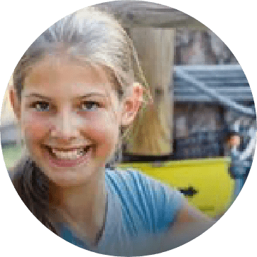 young girl smiling on a zip line