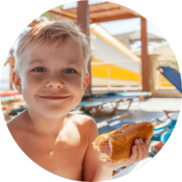 young boy smiling while eating a hot dog outside