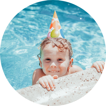 little boy at the edge of a pool with a birthday hat on