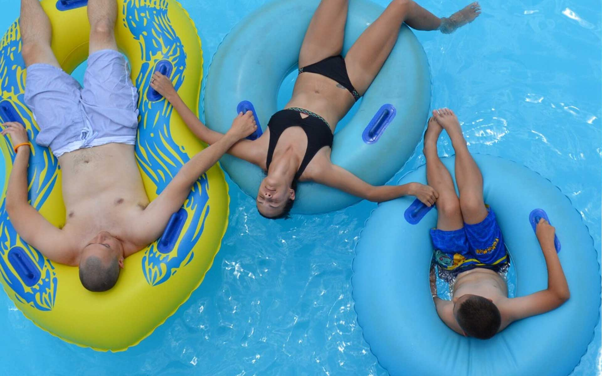 a family of three relaxing in a pool lying down on floats