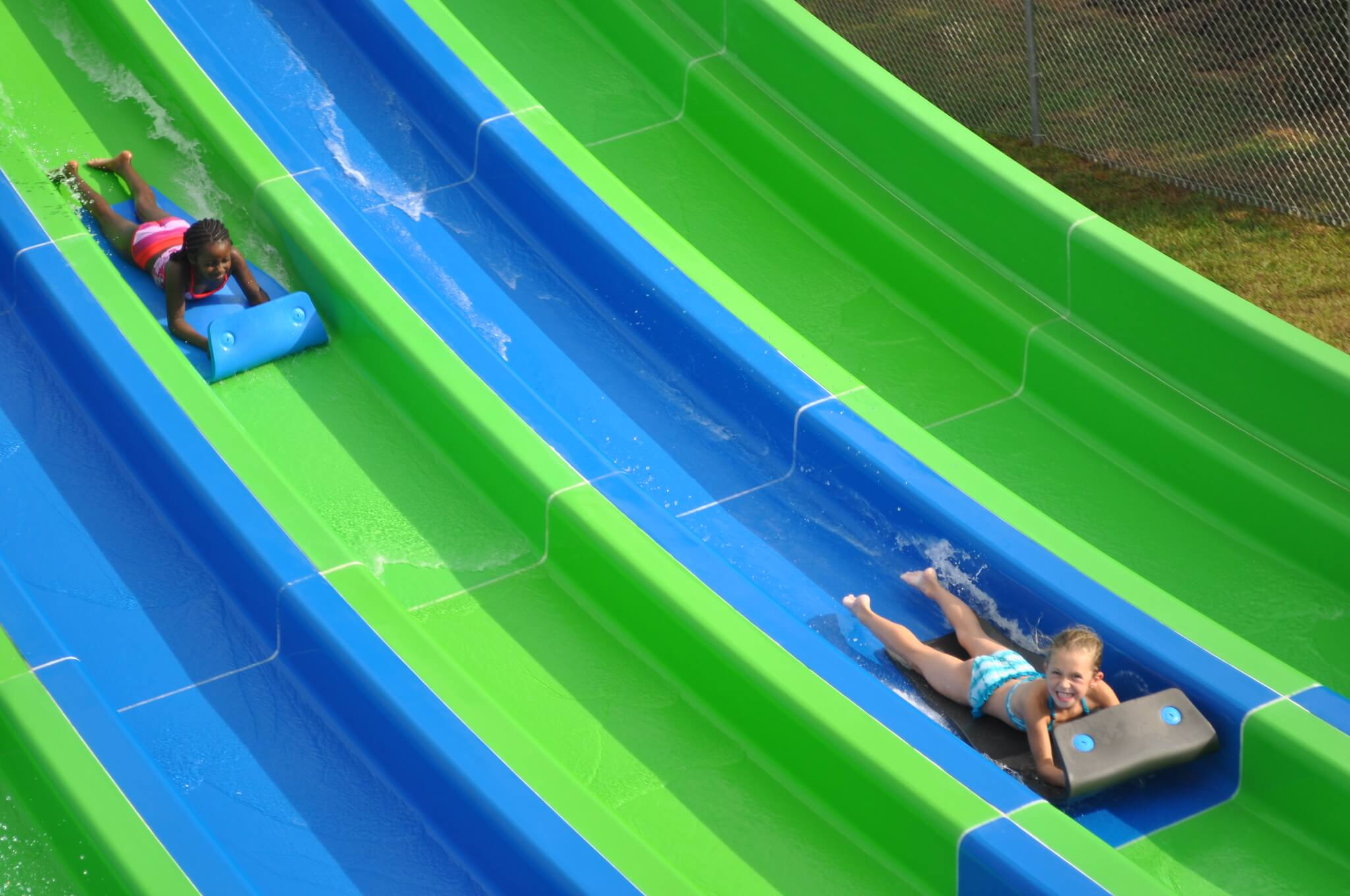 two kids sliding down a blue and green waterslide