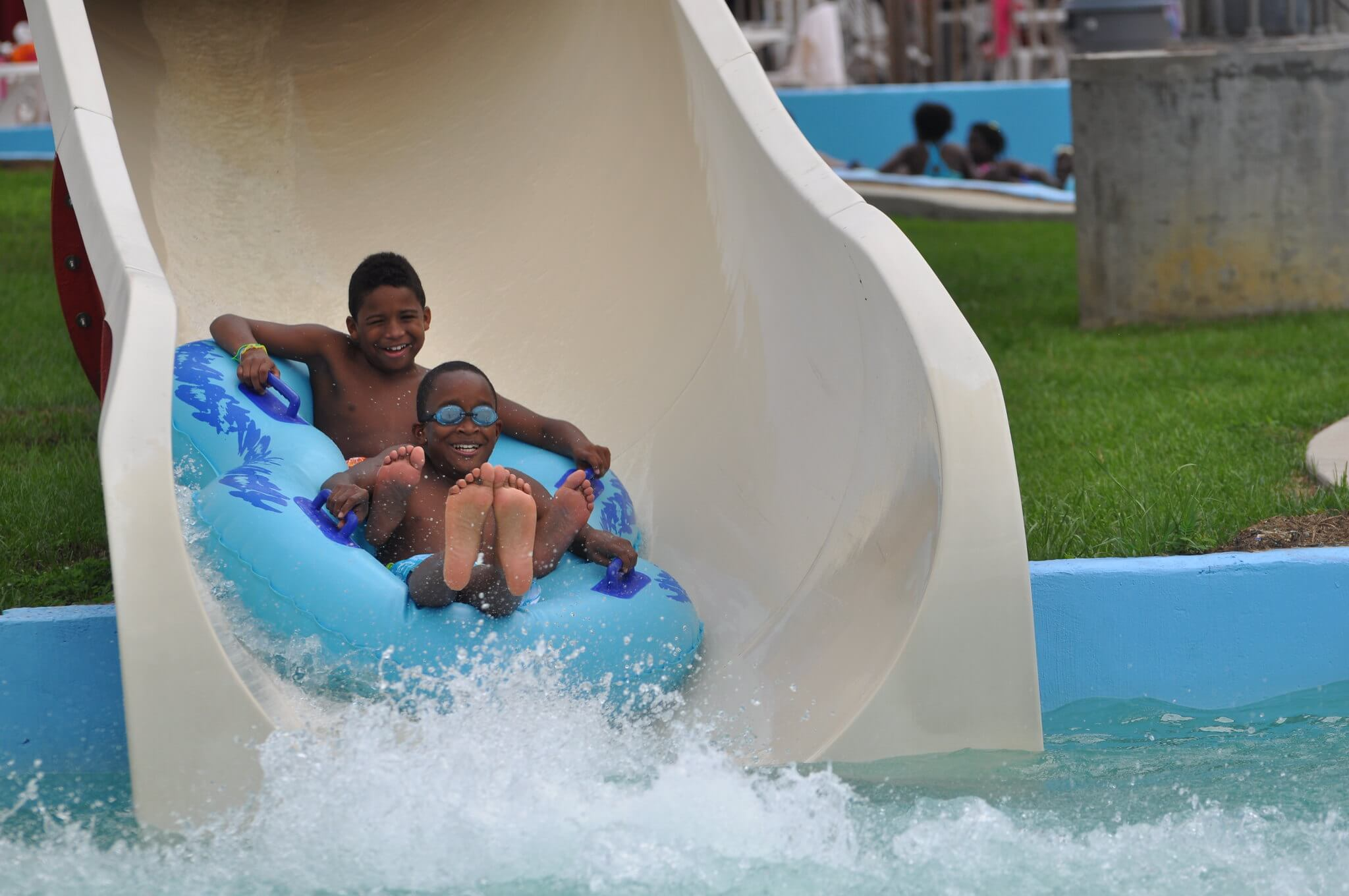 two young black boys on a float sliding down a waterslide about to land in a pool