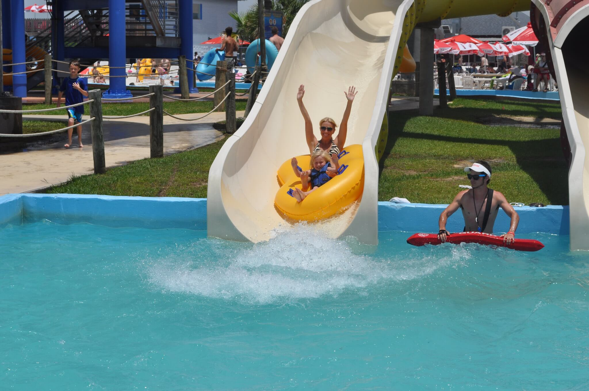 mom and child sliding down waterslide with hands in the air, lifeguard standing in the pool