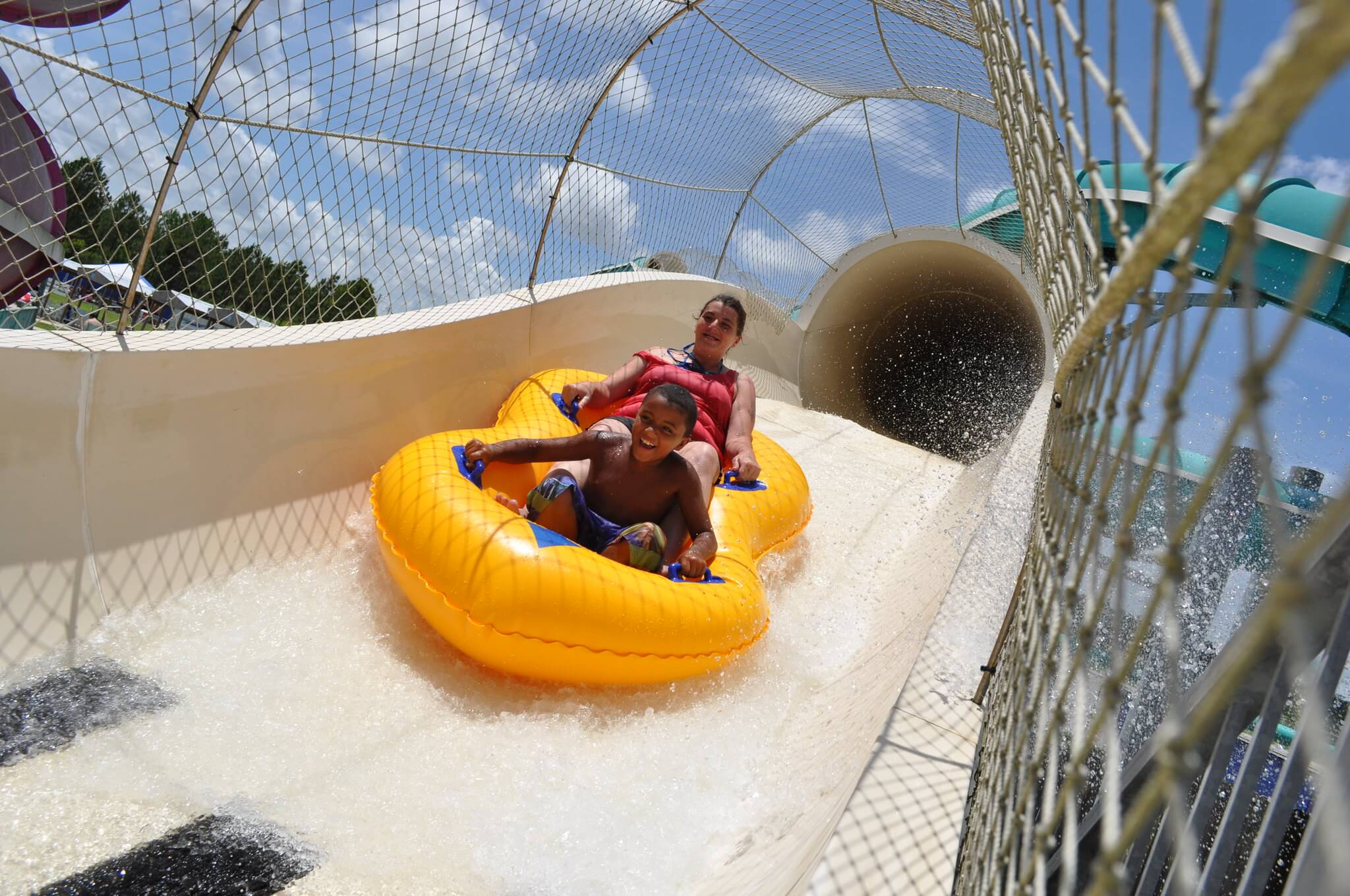 a girl and young boy on a yellow float coming out of a tunnel in a waterslide