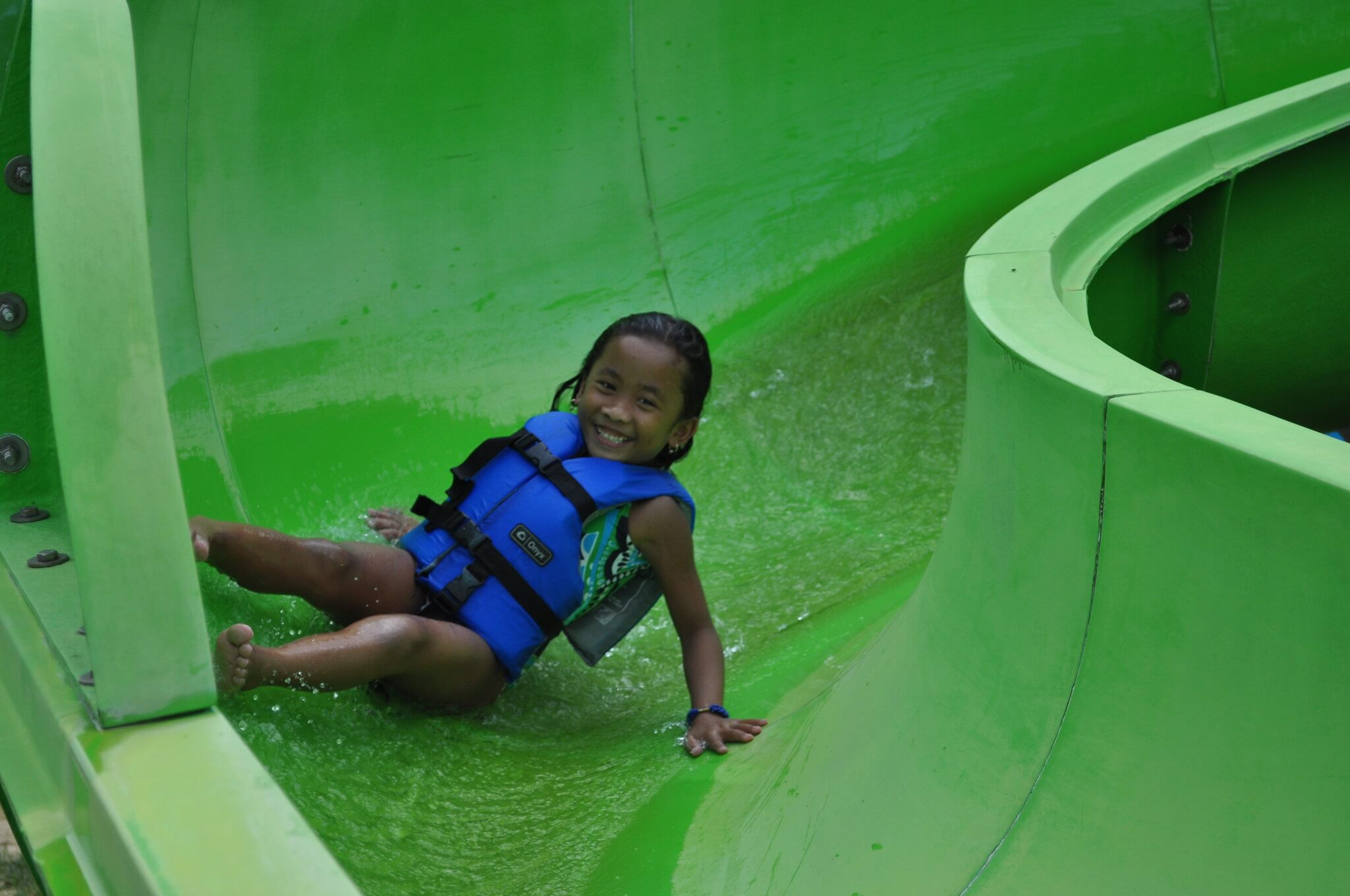 a young black boy sliding down a green slide in a life jacket