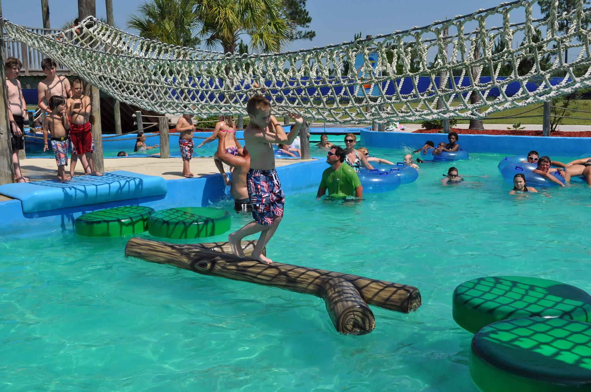 young kid crossing the pool on a log while holding onto rope