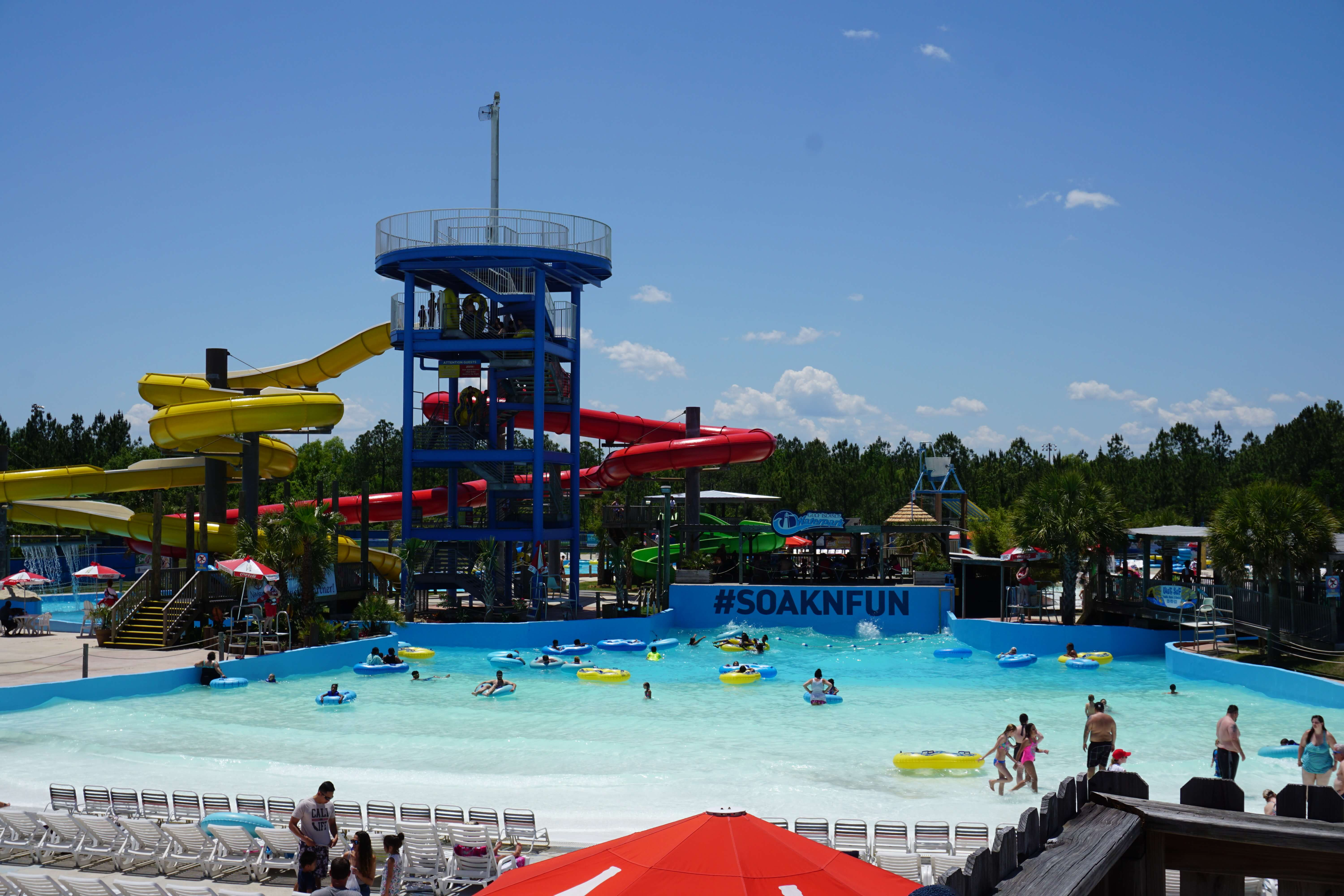 wide view of various slides, wave pool, and chairs at waterpark