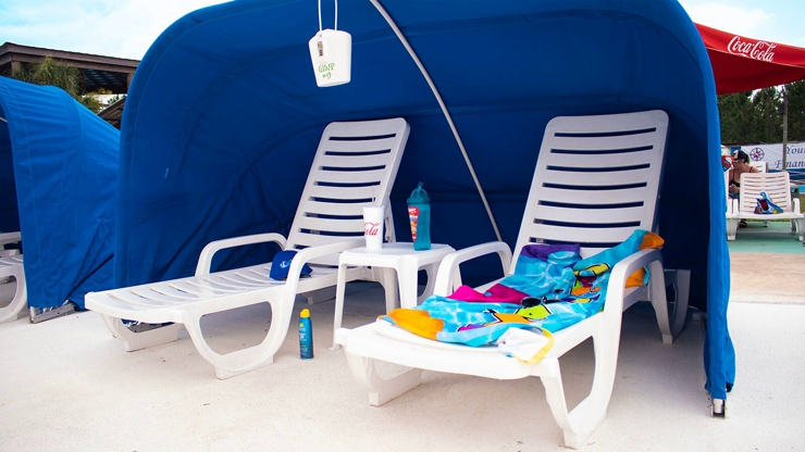 Two lounge chairs under a blue cabana