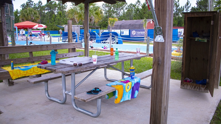 Picnic table with drinks and towels, private locker under the shade.