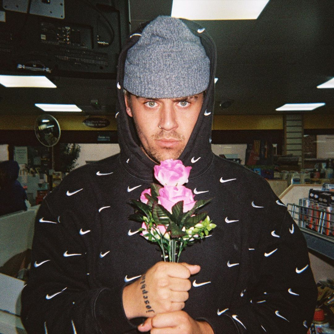 Man in a Nike hoodie holding a flower