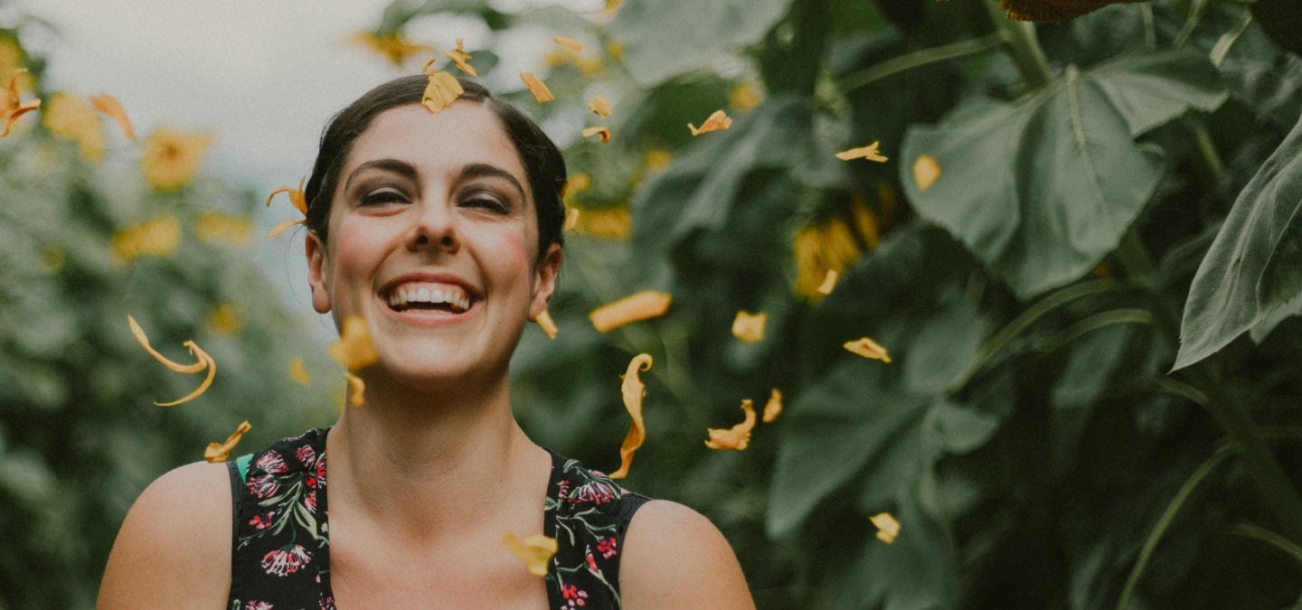 Happy woman with yellow petals raining down on her.