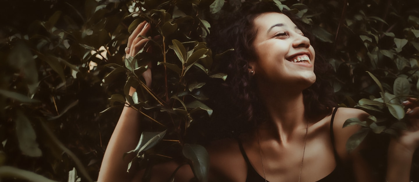 Joyous woman holding onto and surrounded by rhododendron, smiling with eyes closed and face turned up into the light.