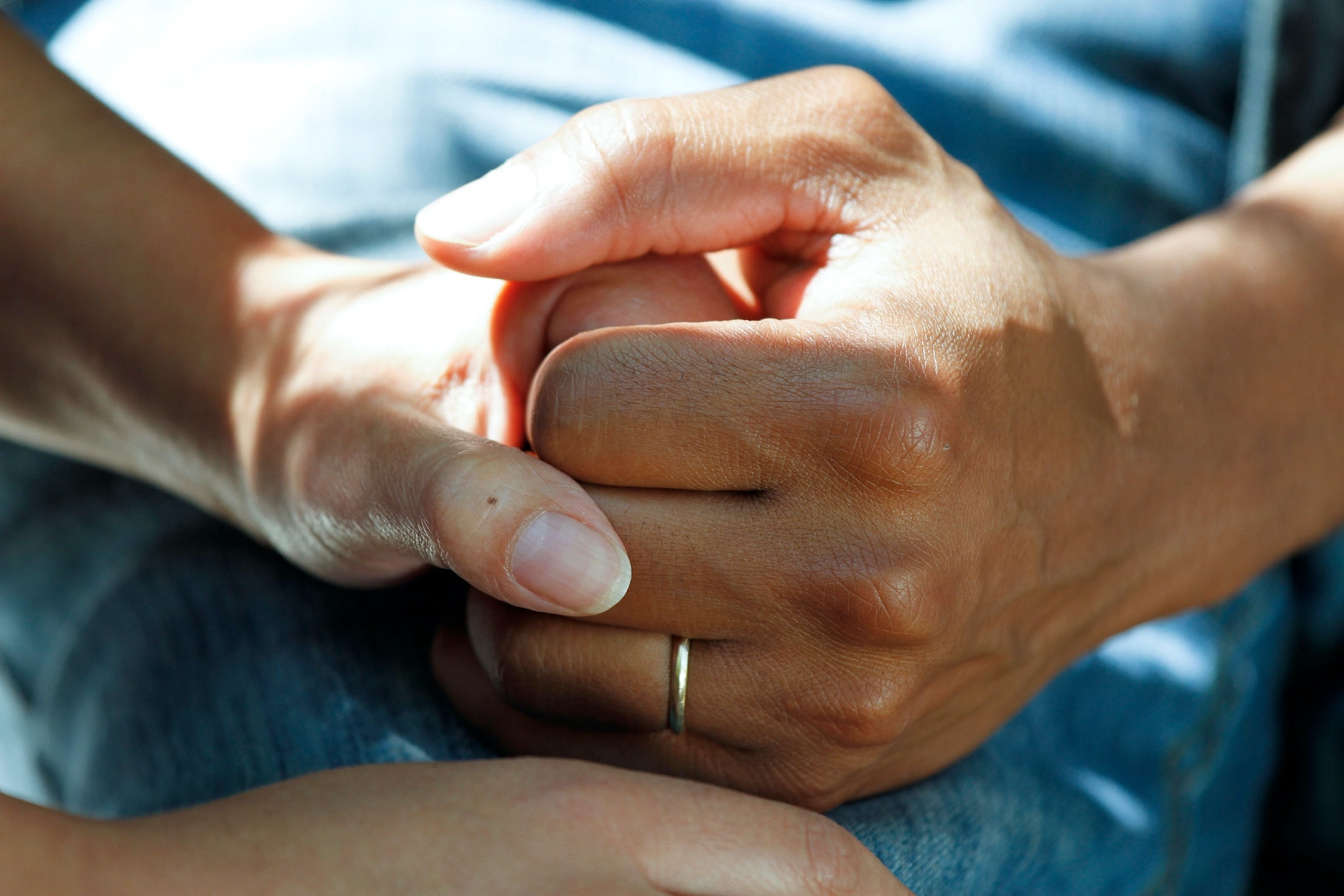 Two people's hands clasping.
