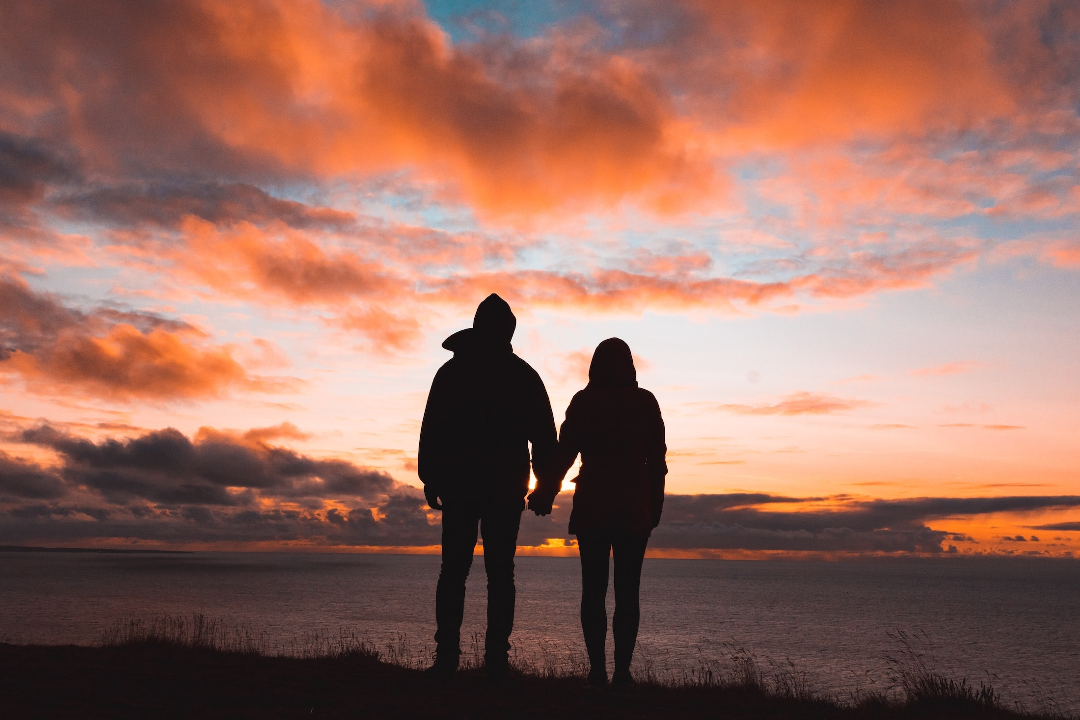 Silhouetted couple holding hands in front of a sunset over water.