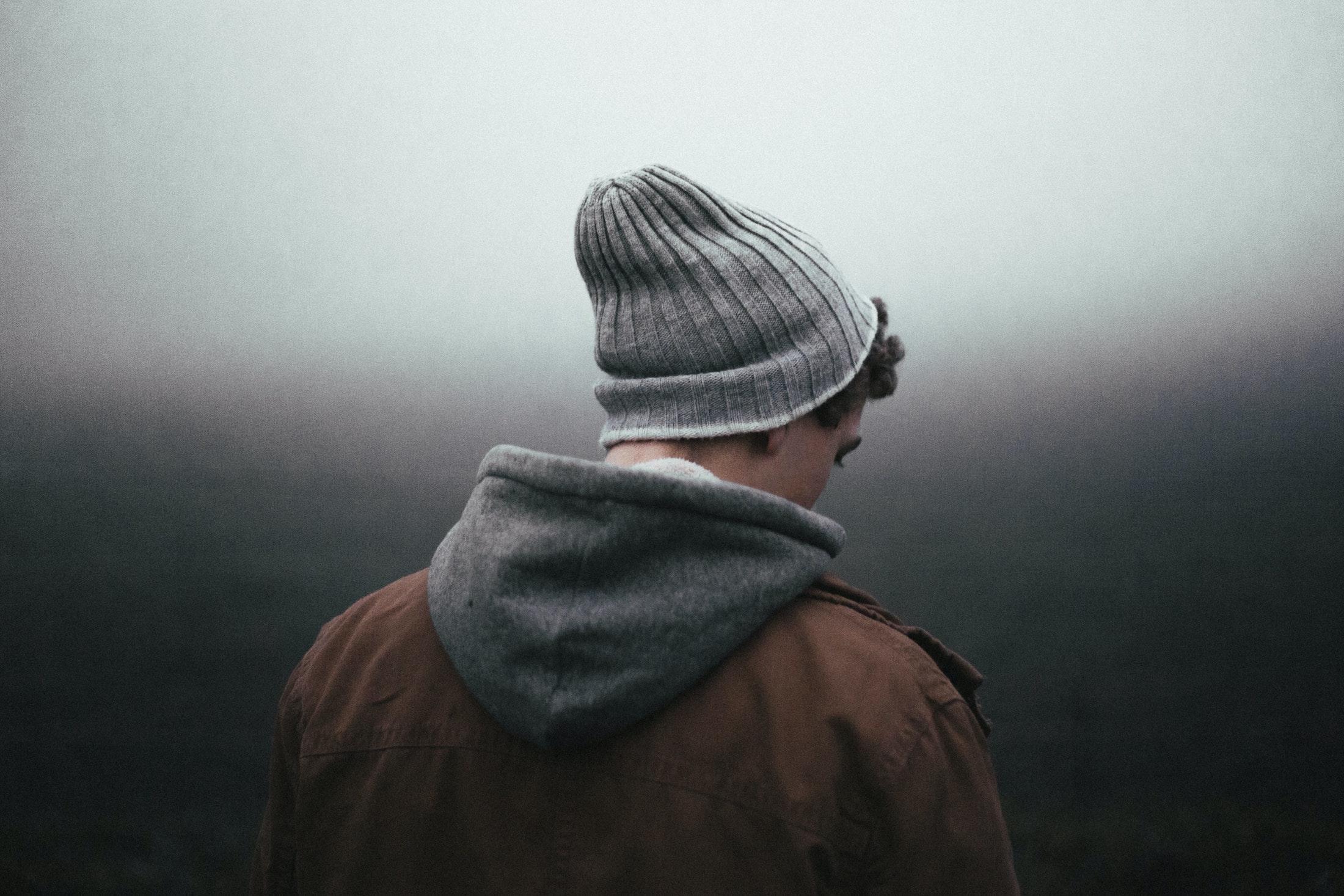 Man looking downward, viewed from behind.