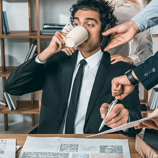 portrait of busy businessman drinking coffee and sitting at workplace while colleagues helping with work in office