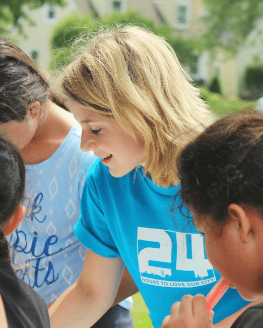 Female charity worker surrounded by kids
