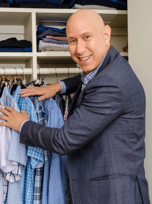 A sharply dressed Andrew Mellen sorting through a closet, smiling at the camera.