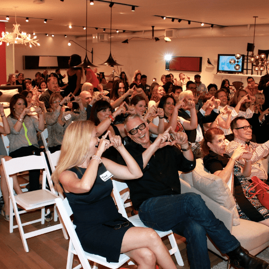 A packed room performing Andrews signature 'organizational triangle' during one of his public talks.