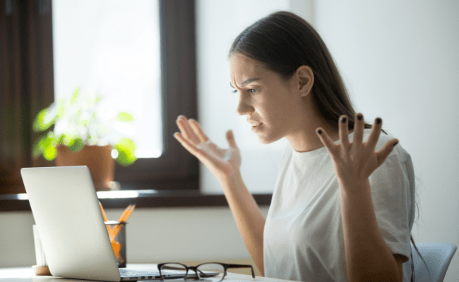 Young adult woman looking in laptop computer, fling arms up.