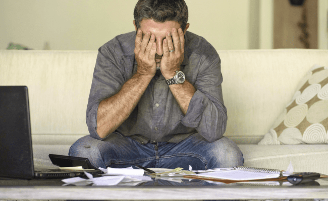 Man at home doing domestic accounting with paperwork and calculator feeling overwhelmed and worried.