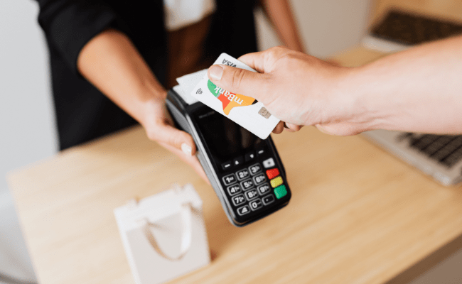 Man extending his arm to tap and purchase using his credit card on merchants contactless machine.