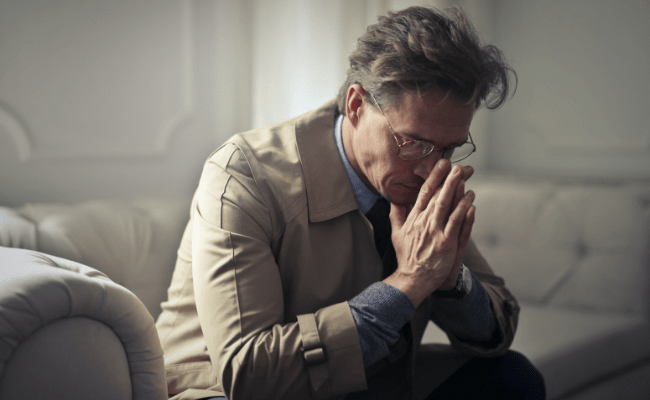 Older man at home feeling overwhelmed and worried, clasping his hands in thought.