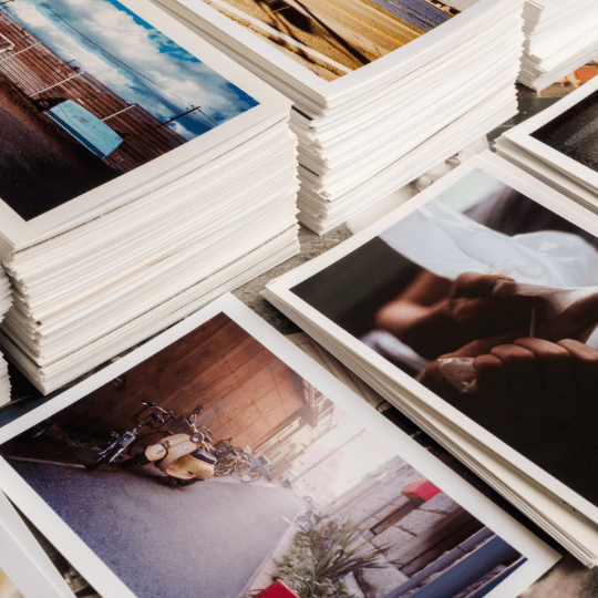 Neatly organized photos stacked and neatly displayed on a natural wooden table.