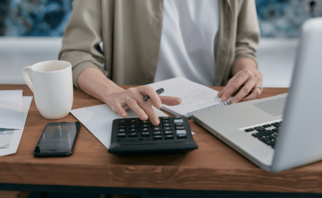 Woman performing personal finances at home, using calculator with one hand whilst another holds a notepad in place.
