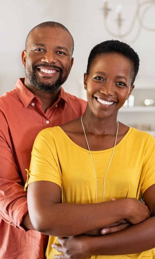 Middle aged couple embracing whilst smiling at the camera.