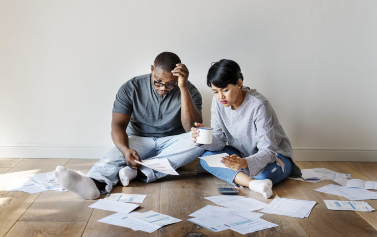Middle aged couple sitting on a a wooden floor in an empty room, going through mountains of back dated bills and finances.