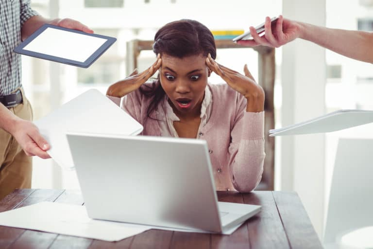 Woman clearly stressed at work, co-workers either side of her handing her projects while she sits with her hands on her head looking overwhelmed.