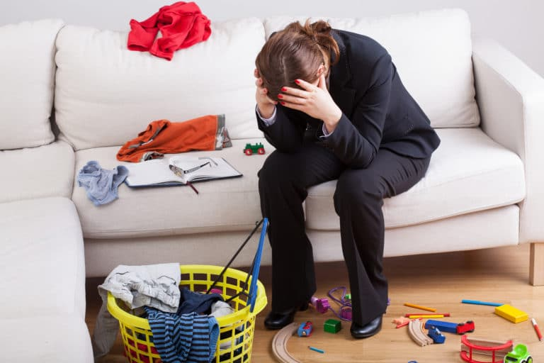 Woman with her head in her hands, frustrated and at a loss with the messy home surrounding her.