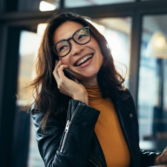 Smiling business woman in casuals talking on phone