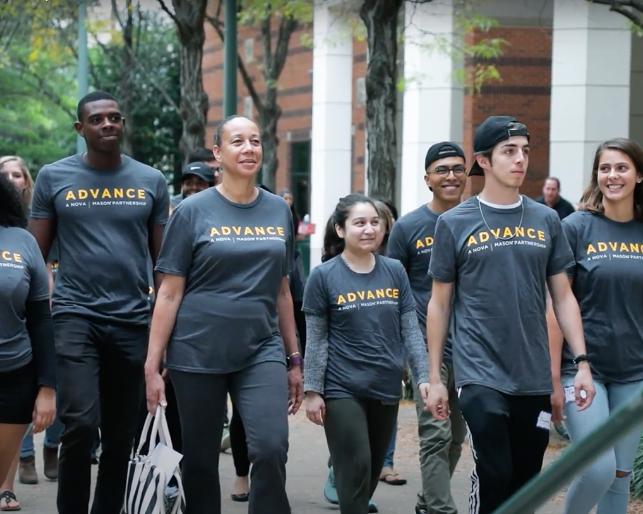 College students walk around campus wearing ADVANCE tshirts