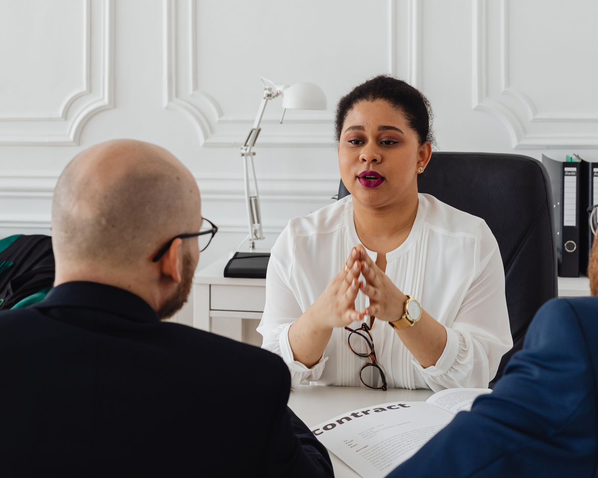 Business woman sitting at table talking to two clients