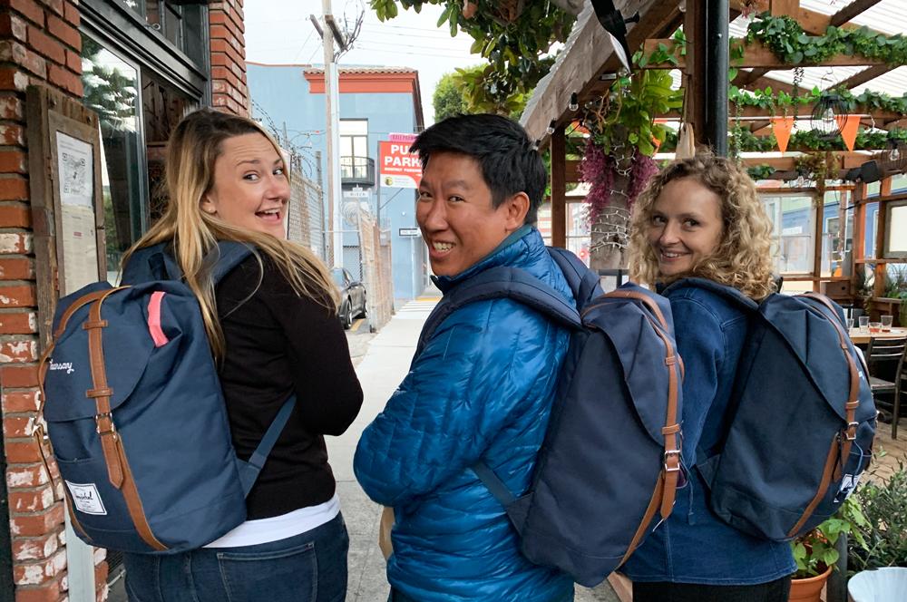 Three Hearsay team members wearing backpack and smiling