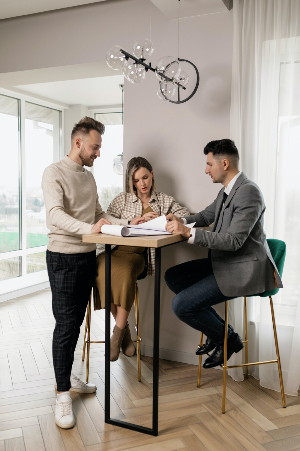 A couple talking to an agent inside a home