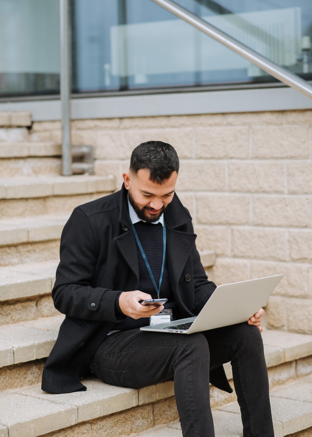 Business man sitting on steps texting