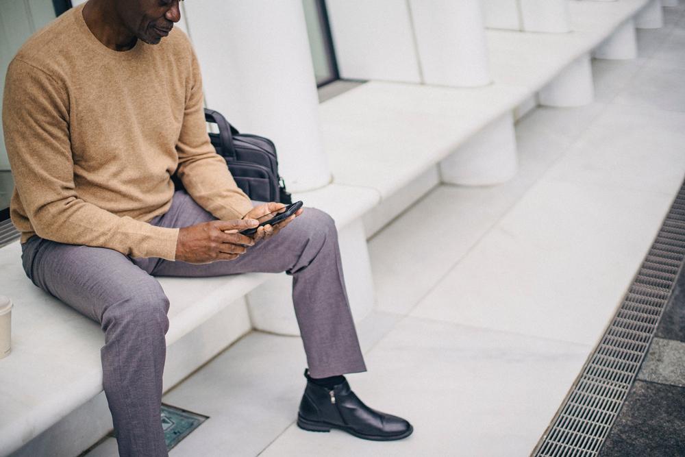 Man texting on bench