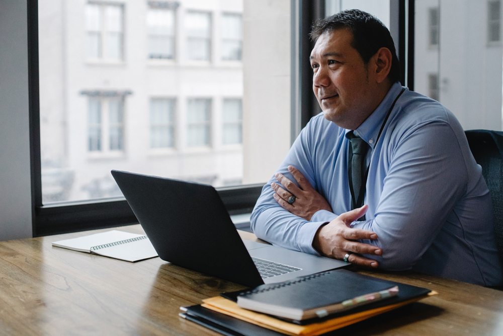 Business man sitting at desk in front of laptop