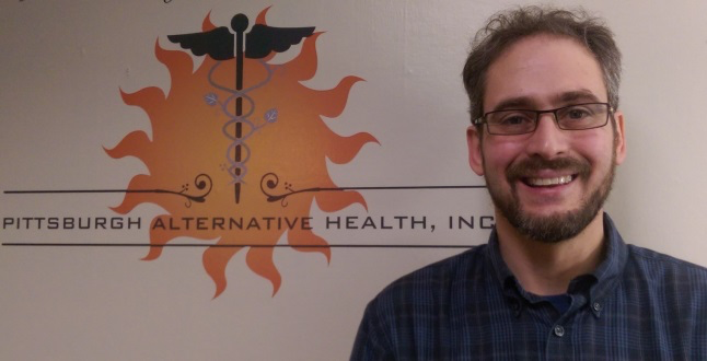 Darrell standing in front of Pittsburgh Alternative Health sign
