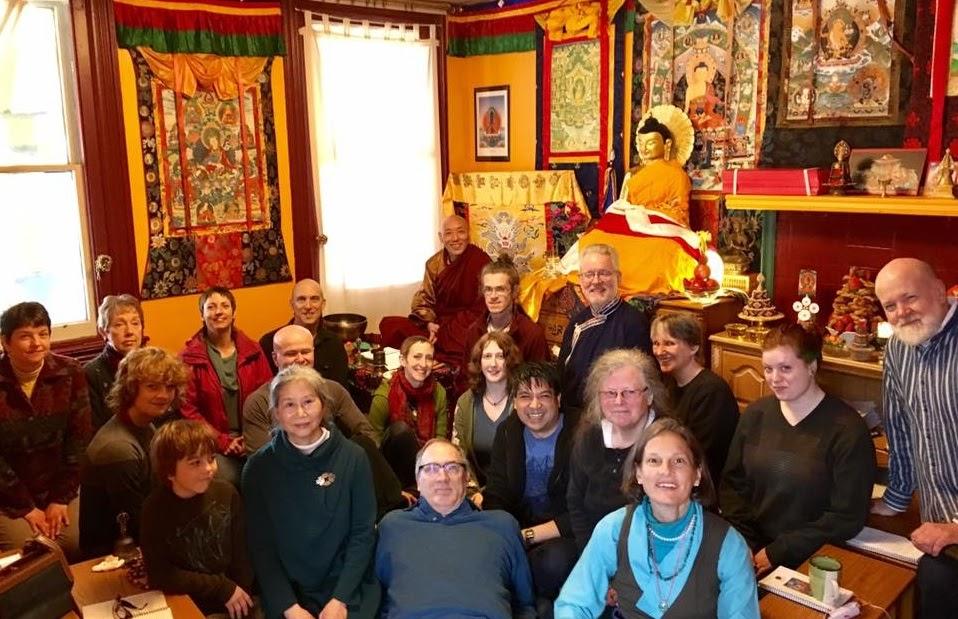 Group of people kneeling on floor of Tibetan meditation room