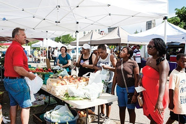 Patrons standing at farmers market stand