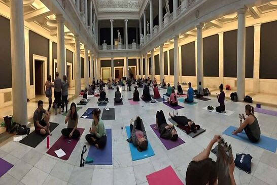 People practicing yoga in a museum.